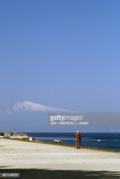 Mount Etna covered with snow seen from Reggio Calabria Sicily Italy