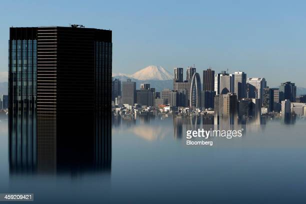 Mount Fuji and buildings are reflected on a table at an observation deck in Tokyo Japan on Tuesday Dec 24 2013 Japan unveiled a record budget for the...