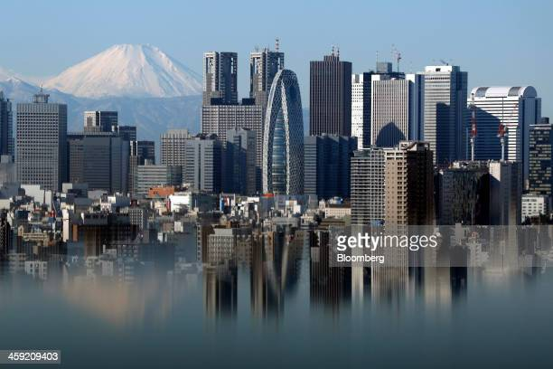 Mount Fuji and buildings in the Shinjuku district are reflected on a table at an observation deck in Tokyo Japan on Tuesday Dec 24 2013 Japan...