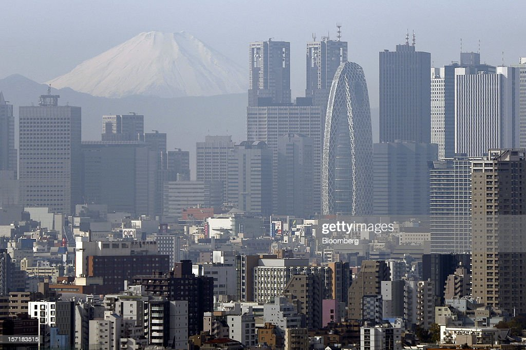 Mount Fuji emerges through buildings in the Shinjuku district of Tokyo, Japan, on Thursday, Nov. 29, 2012. Japan's cabinet approved a second round of fiscal stimulus worth 880 billion yen ($10.7 billion) using budget reserves as Prime Minister Yoshihiko Noda attempts to boost the economy before elections on Dec. 16. Photographer: Kiyoshi Ota/Bloomberg via Getty Images