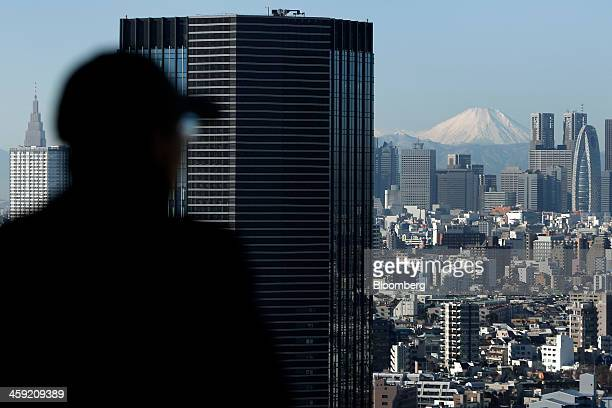 Mount Fuji stands behind buildings as a visitor looks out at the skyline from an observation deck in Tokyo Japan on Tuesday Dec 24 2013 Japan...