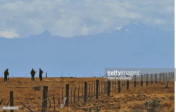 Mount Kenya is seen in the background as armed Game Rangers survey the Ol Pejeta Conservancy on February 6 which borders community owned lands The...