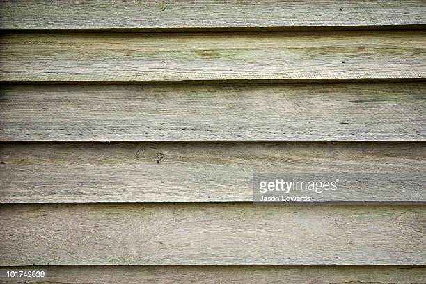 Pine timber slats overlap and seal one another on a workshop wall.