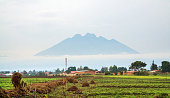 The Mt Sabinyo volcano seen from the city of Musanze (former Ruhengeri) surrounded by early morning mist. It stands at the border of Rwanda, Uganda and DRC in the heart of Volcanoes National Park. The
