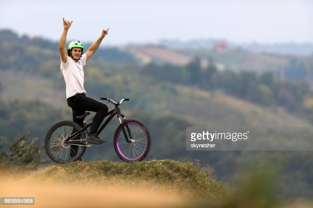 Mountain bike cyclist with arms raised on top of hill.