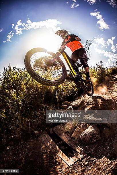 Mountain biker about to dirt jump over rough terrain