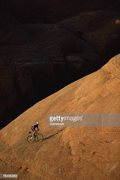 Mountain biker ascending rock formation , Moab , Utah