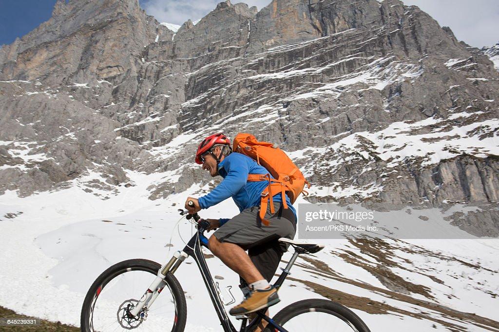 Mountain Biker Ascends Steep Mtn Ridge Near Snow Stock Photo
