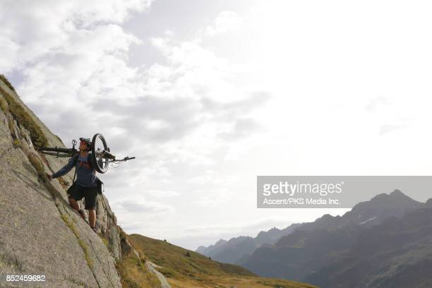 Mountain biker ascends steep rock slabs above valley