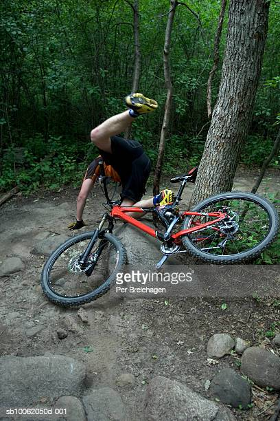 Mountain biker crashing in forest