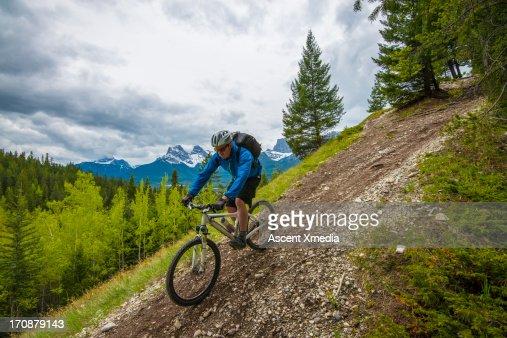 Mountain biker decends steep trail, mtns : Stock Photo