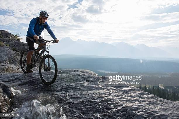 Mountain biker descends rock slab beside creek