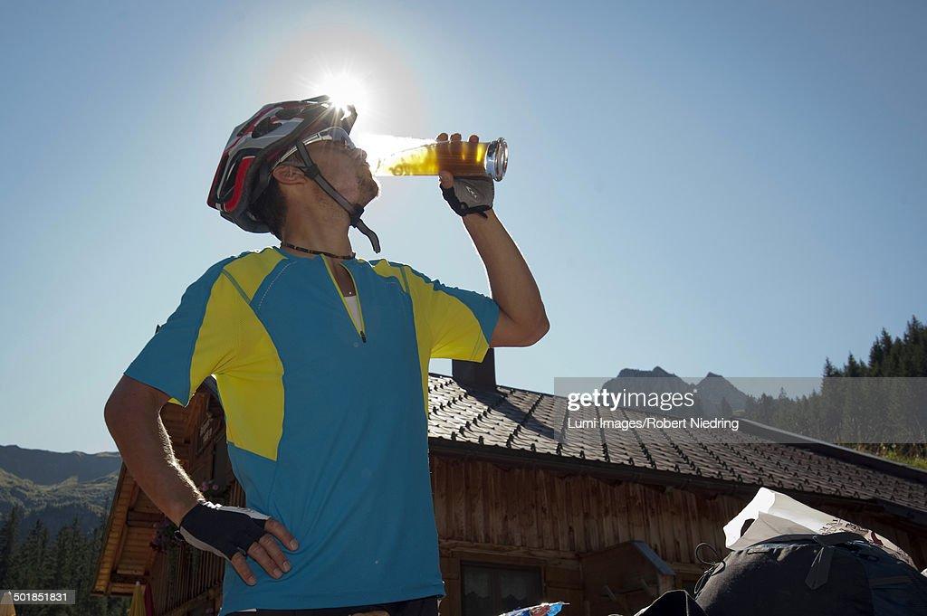 Mountain biker drinking a beer, Kleinwalsertal, Vorarlberg, Austria : Stock Photo