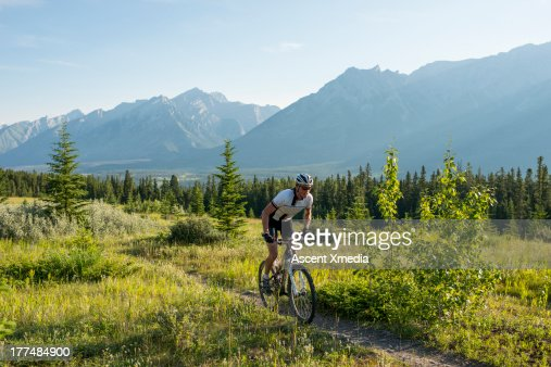Mountain biker follows trail uphill through mtns : Stock Photo