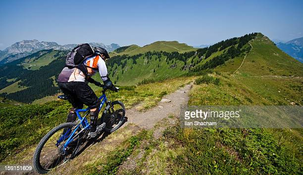 Mountain biker going down the ridge in the alps