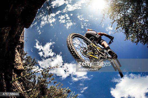 Mountain biker jumping through the air on an off-road trail