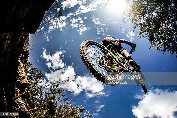 Mountain biker jumping through the air on an off-road trail