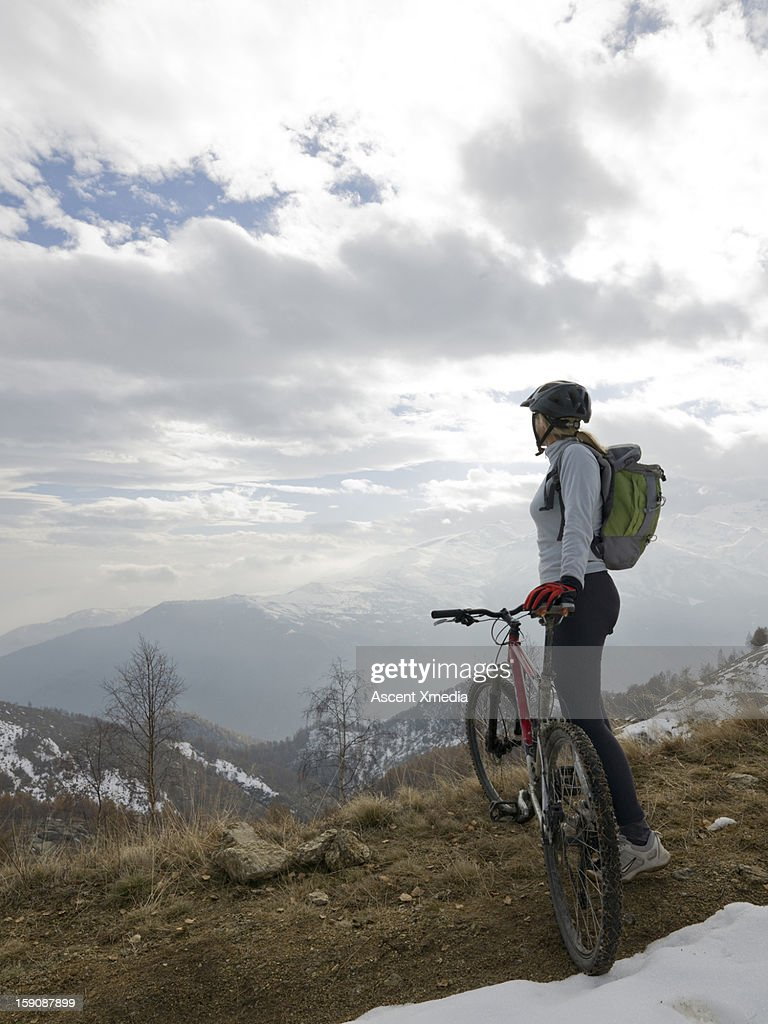 Mountain biker looks out across snowy mt landscape : Stock Photo