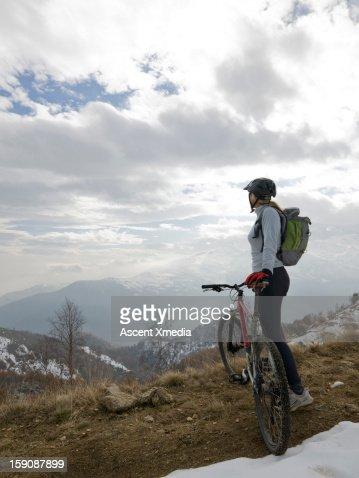 Mountain biker looks out across snowy mt landscape : Stock Photo