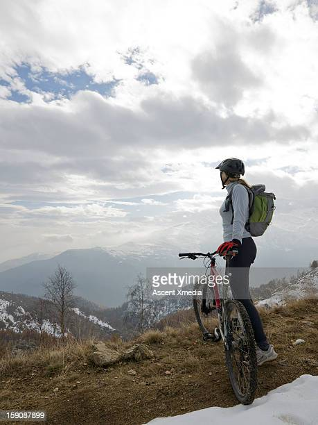 Mountain biker looks out across snowy mt landscape