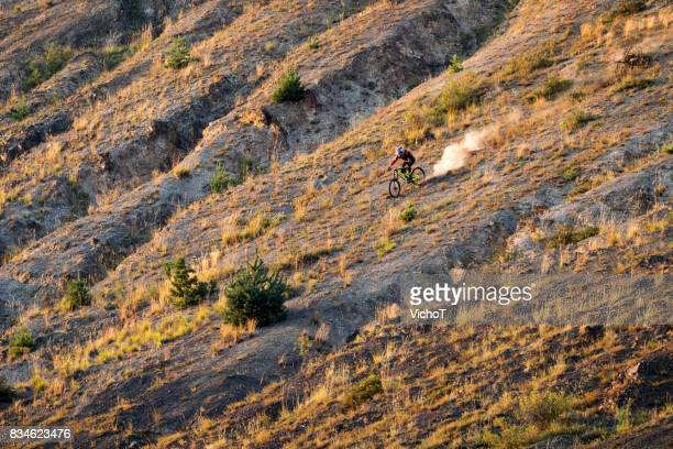 Mountain biker making a freeride descent on a steep slope in the evening