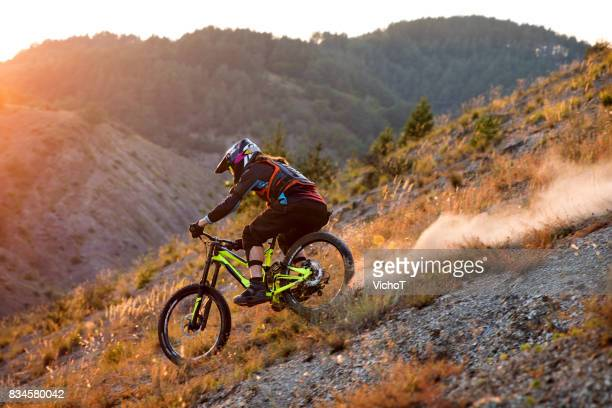 Mountain biker making a freeride descent on a sunset