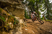 A mountain biker on a singeltrack trail in woodland in the Verbier region of Switzerland.