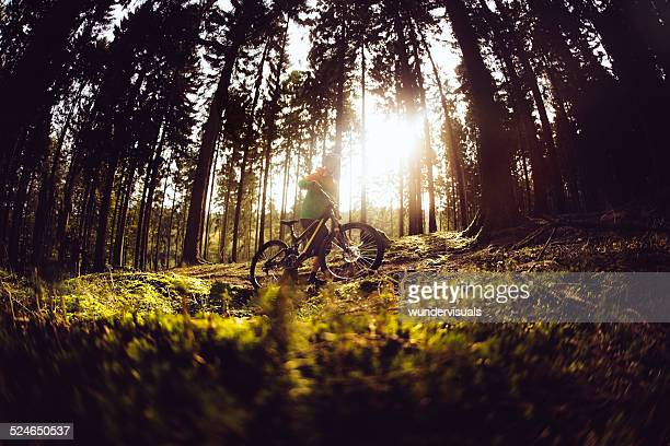 Mountain Biker Pushes His Bike Up The Track In Forest