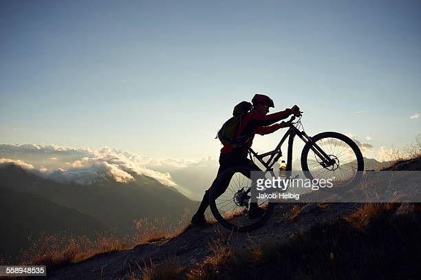Mountain biker pushing bike uphill, Valais, Switzerland