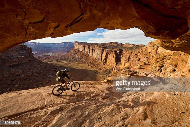 A mountain biker rides by on slickrock with dramatic desert scenery in the background.