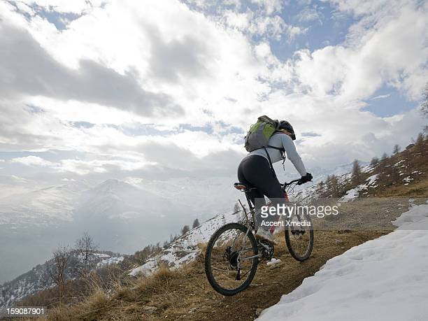 Mountain biker rides up mountain track by snow
