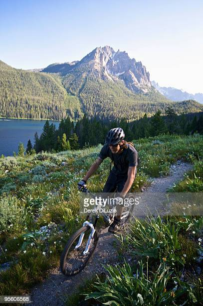 A mountain biker riding around a lake in Idaho with mountains in the distance.