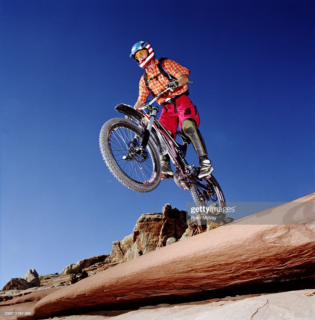 Mountain biker riding down rocky terrain, low angle view : Stock Photo