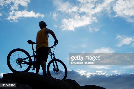 mountain biker silhouette with blue sky clouds stock photo getty images