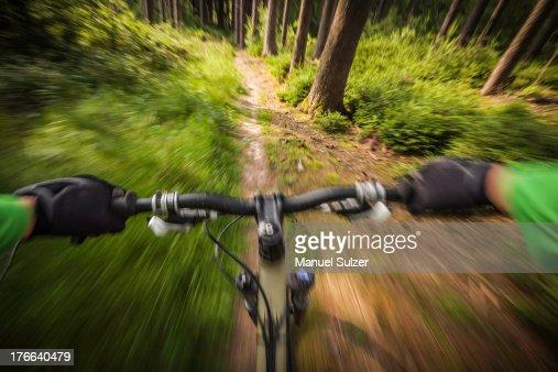 Mountain biker speeding down forest path