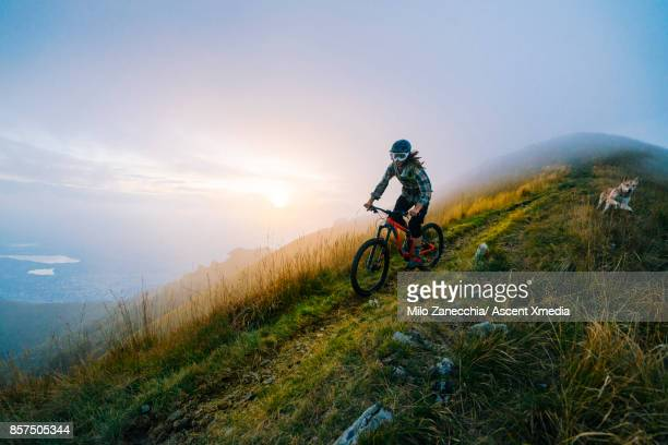 Mountain biker traverses high mountain ridge, with dog