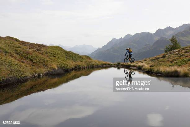 Mountain biker traverses trail beside alpine pond
