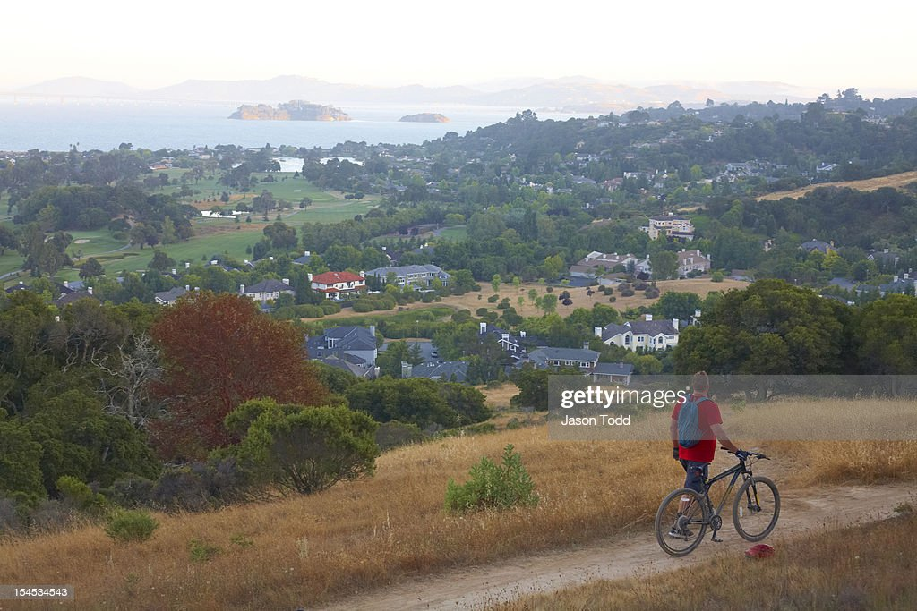 Mountain biker walking bicycle along bay view.