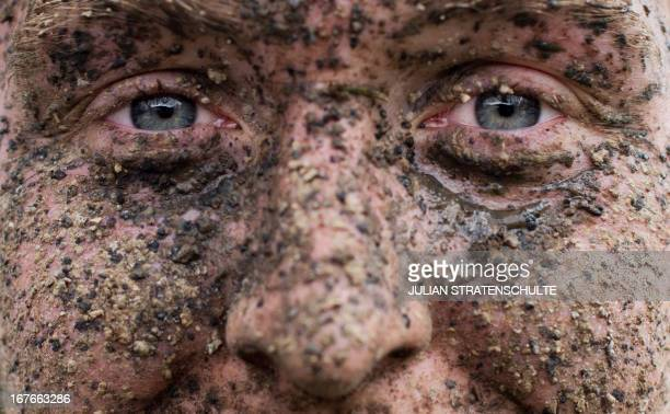 A mountain biker with a mudcovered face smiles as he passes the finishing line of the mountain bike festival 'MegaSports' in SundernHagen western...