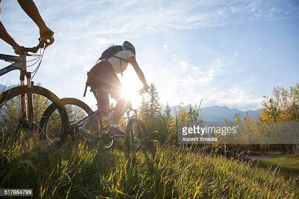 Mountain bikers descend mtn ridge crest, autumn