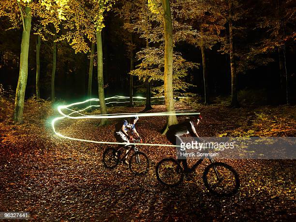 Mountain bikers making light trails in forest