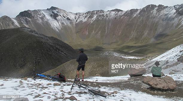 Mountain bikers on a break take in the snowy vista at the lip of a crater atop Nevado de Toluca in Mexico July 7 2012