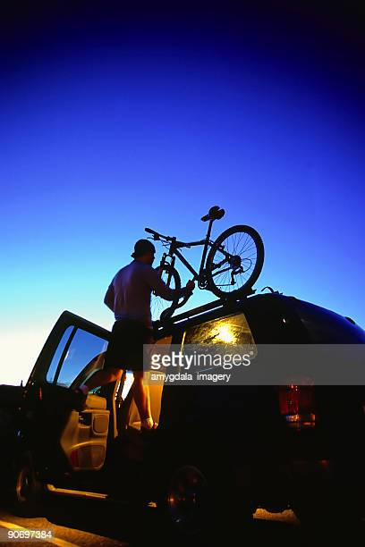 mountain biking man loading bike on SUV twilight sky