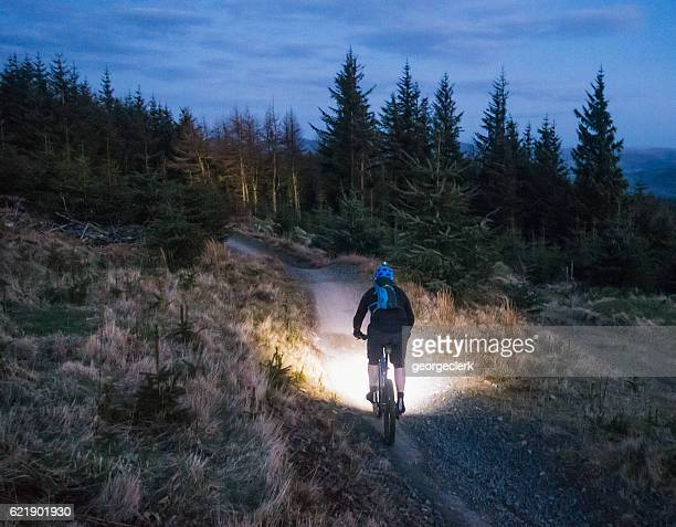 Mountain biking with lights at dusk
