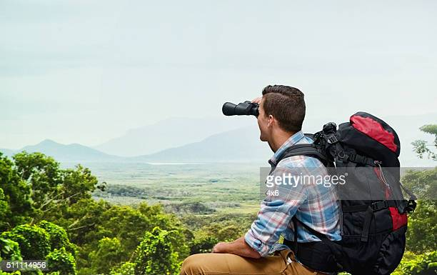Mountain climber looking through binocular
