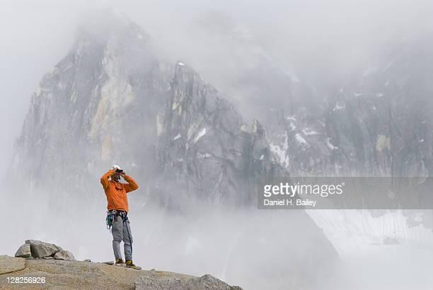 Mountain climber looking through binoculars