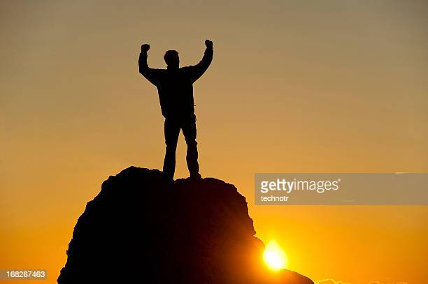 Mountain climber reaching the top at sunset