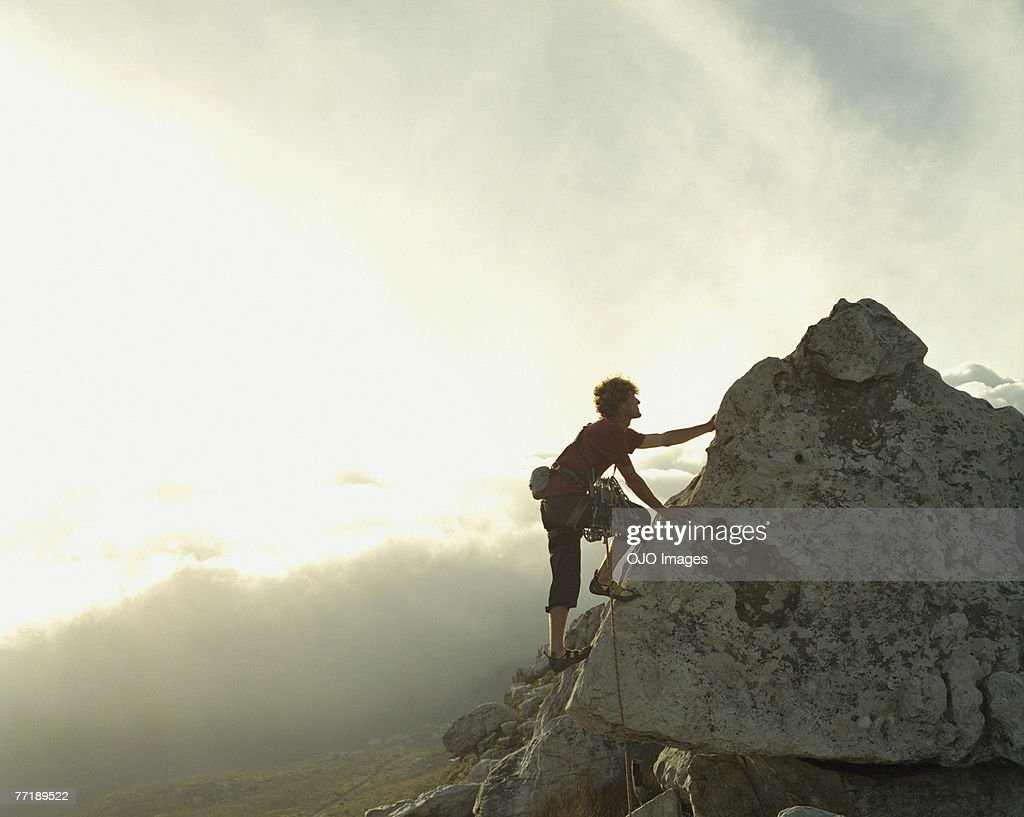 A mountain climber reaching the top of a mountain : Stock Photo