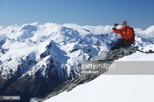 Mountain climber taking a picture on mountain peak : Stock Photo