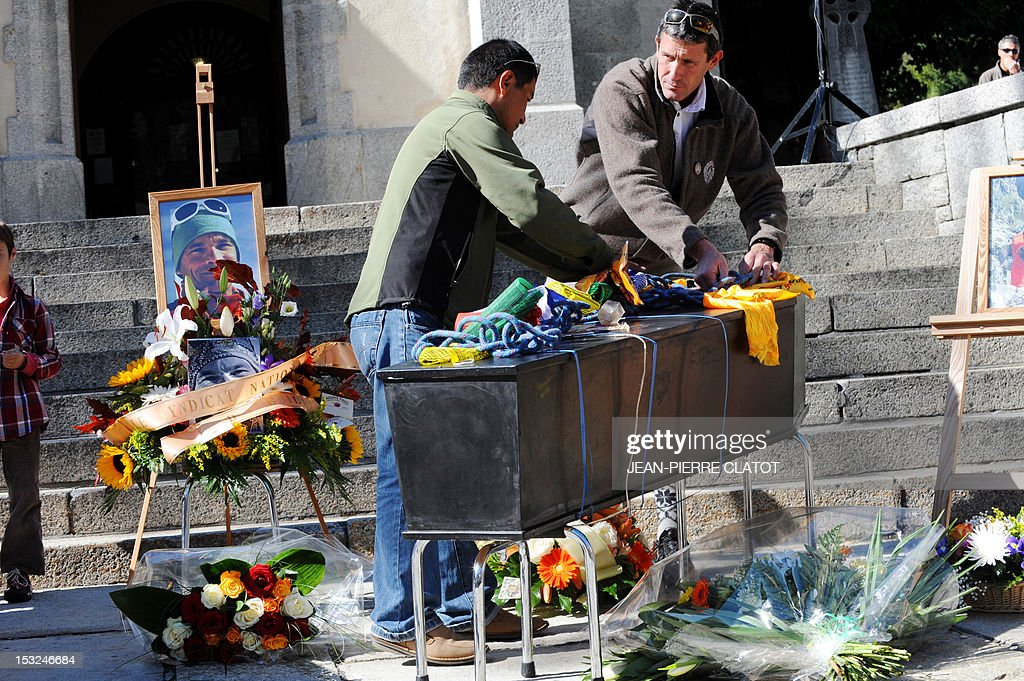 Mountain climbers put on the coffin of one of their colleagues, climbing material and Tibetan flags during a memorial ceremony to pay tribute to the victims of the last week avalanche on Nepal's Manaslu mountain, on October 2, 2012, in Chamonix, that is considered the birthplace of European alpinism and the home of most of the French climbers killed. The four French -- two guides and two clients -- were among eight people killed after an avalanche swept through their camp on the side of the 8,156-metre (26,759-foot) Himalayan mountain, just hours before the alpinists were to make an attempt to reach the peak's summit. At left, the portrait of the climber Remy Lecluse, still missing.